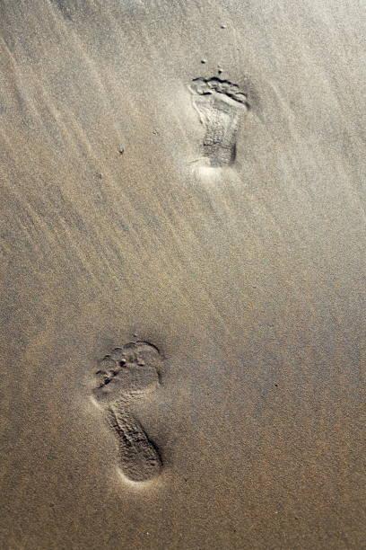 Menschliche Barfuß-Fußabdrücke verschwinden in braungelben SandStrand Hintergrund, Sommerurlaub oder Klimawandel-Konzept, Kopie rand – Foto
