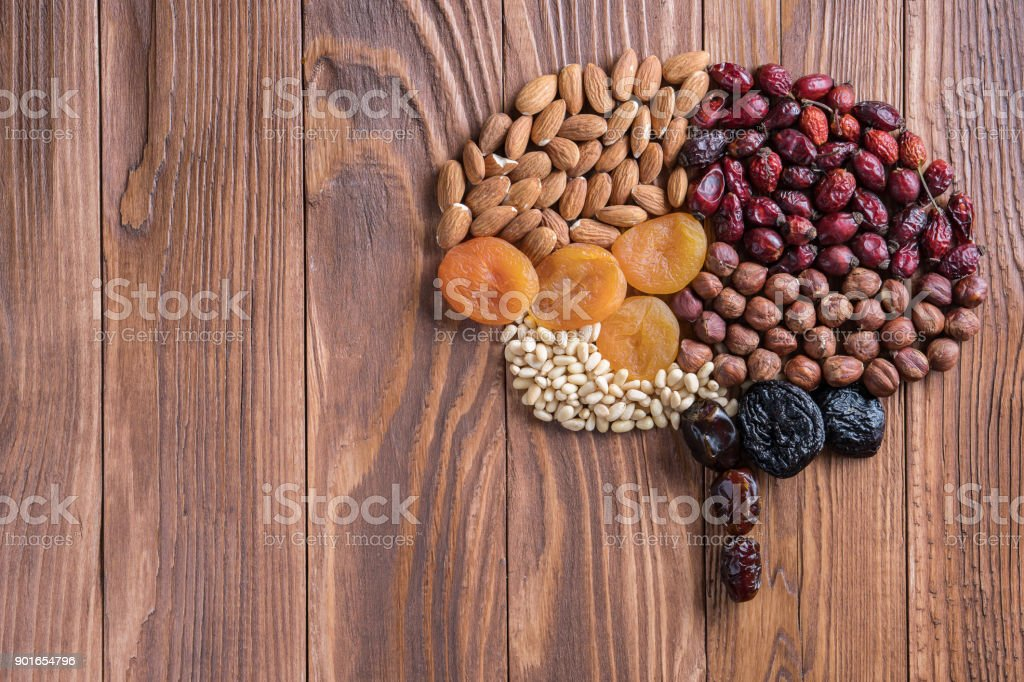 Human brain is made of dried apricots and nuts on a wooden table.   Concept of healthy food. stock photo