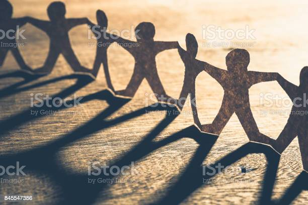 Human chain paper with light and shadow on wood table