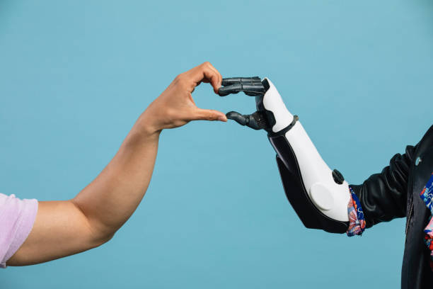Human Connection A human and bionic arm connecting, forming a heart. prosthetic hand stock pictures, royalty-free photos & images