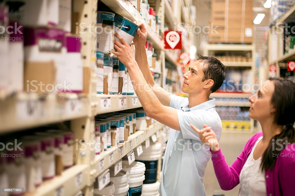 Human couple choosing what kind of paint to buy stock photo