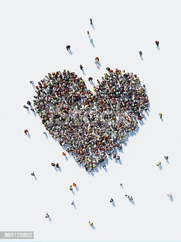 Human crowd forming a big heart shape on white background. Vertical composition with copy space. Clipping path is included. Love and donation concept.