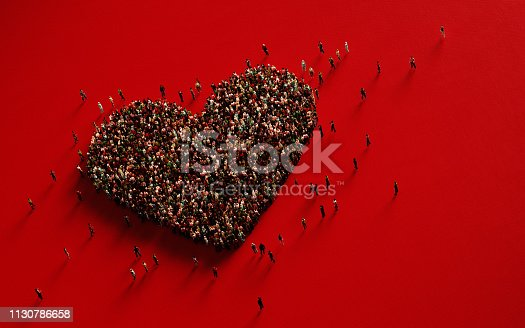 Human crowd forming a big heart shape on red background. Horizontal composition with copy space. Love and donation concept.