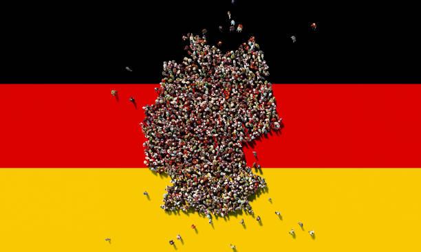 menschliche masse bilden eine deutschland-karte auf deutsche flagge hintergrund: bevölkerung und patriotismus-konzept - demographie deutschland stock-fotos und bilder
