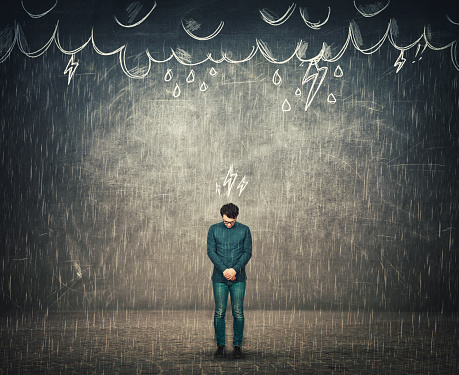 Human depression and emotional breakdown concept, as sad businessman looks down disappointed, has no umbrella protection while stands under the rain, thunderstorm as metaphor for mental health issues.