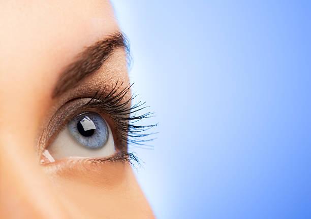Human eye on blue background (shallow DoF) stock photo