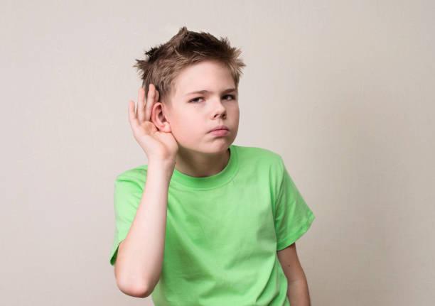 expresión de rostro humano, emoción, lenguaje corporal. curioso chico preadolescente escucha. primer retrato niño escuchando algo, padres hablan, chismes, gesto mano a oreja. - ironía fotografías e imágenes de stock
