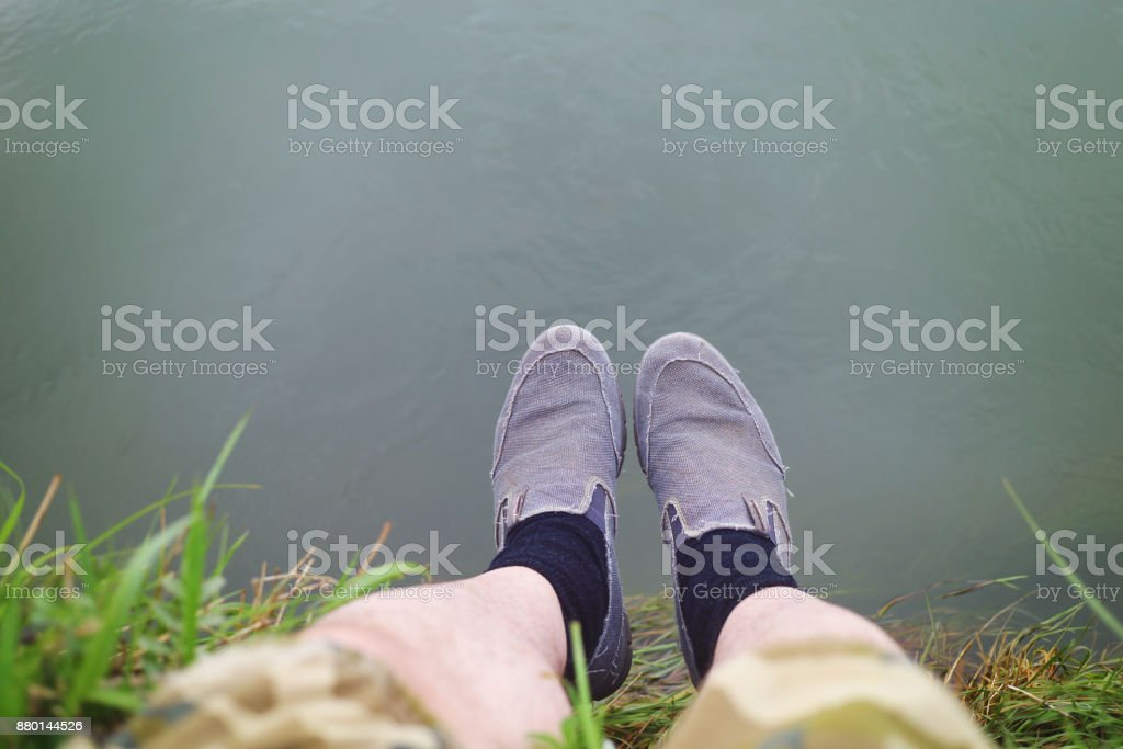 Human feet over river stock photo