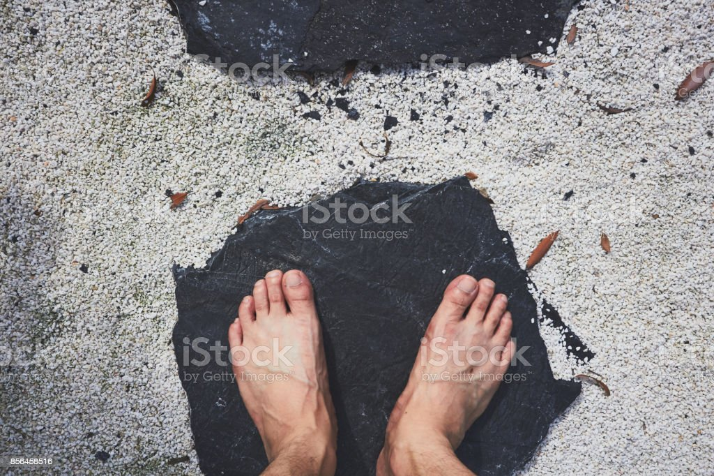 Human feet standing on black stone in white sand stock photo