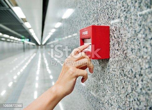 Human finger pushing fire alarm.