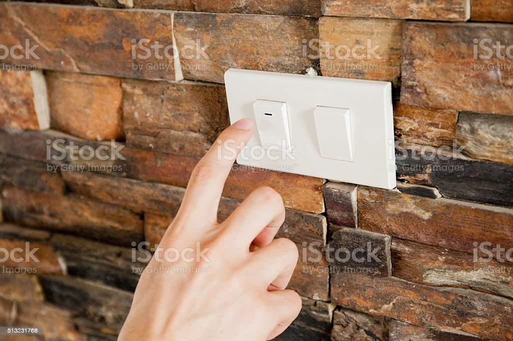 Human finger turning off the light switch stock photo