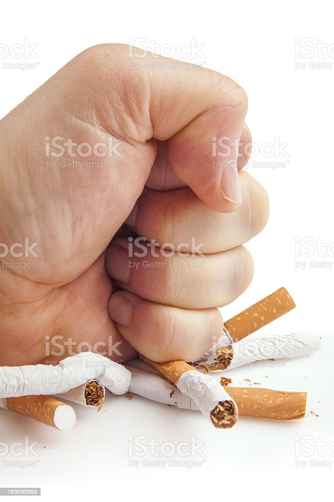 Human fist breaking cigarettes on white background stock photo