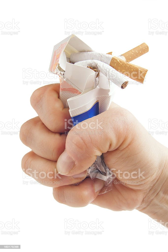 Human fist breaking pack of cigarettes on white background stock photo