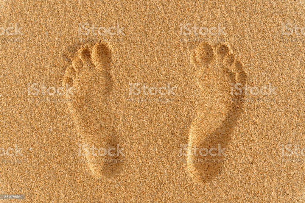 human foot prints on the sand stock photo