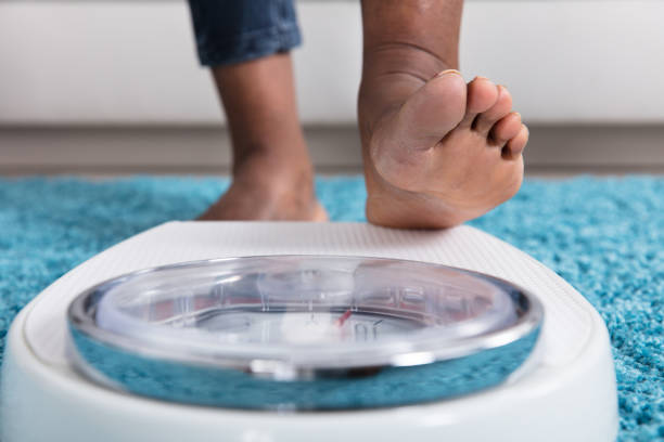 human foot stepping on weighing scale - scale stock photos and pictures