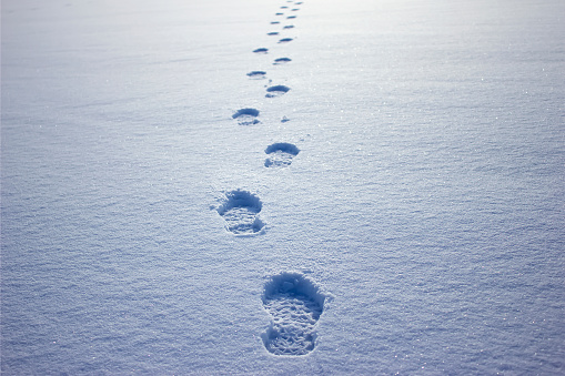 Human footprints in the snow under sunlight close-up view
