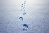istock Human footprints in the snow under sunlight close-up view 1298263597