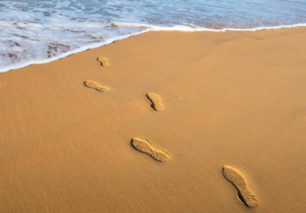 Human footprints on a sandy beach stock photo
