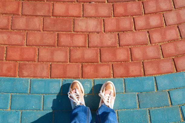 pies humanos en los zapatos de pie en las baldosas del pavimento - foto de stock