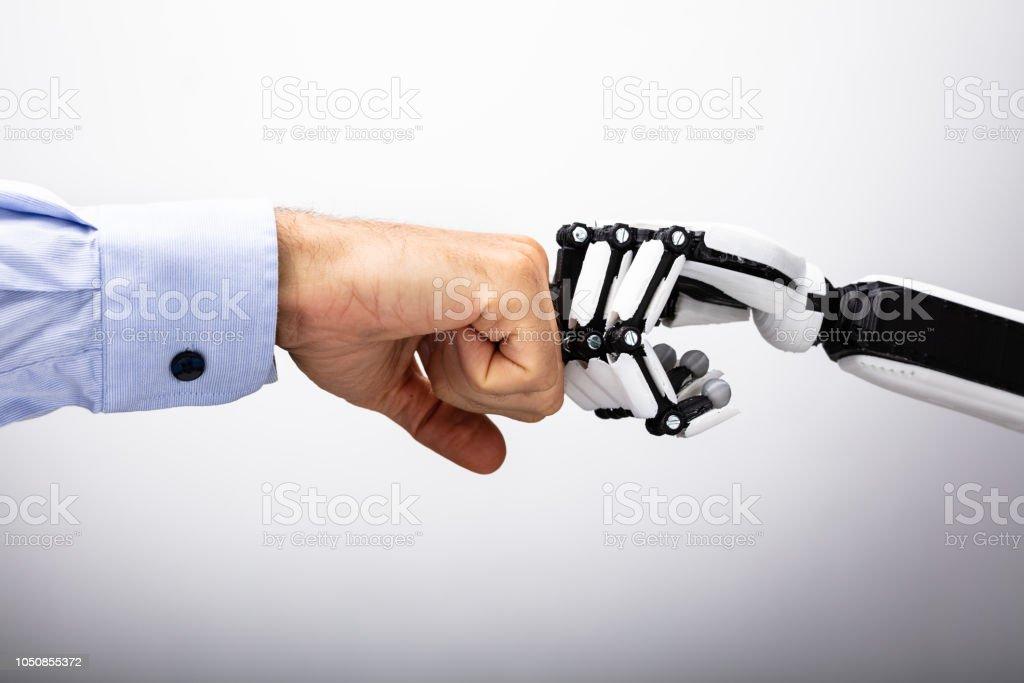 Menschliche Hand und Roboter machen Fist Bump - Lizenzfrei Aggression Stock-Foto