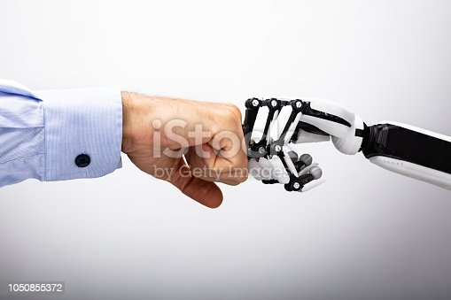 istock Human Hand And Robot Making Fist Bump 1050855372