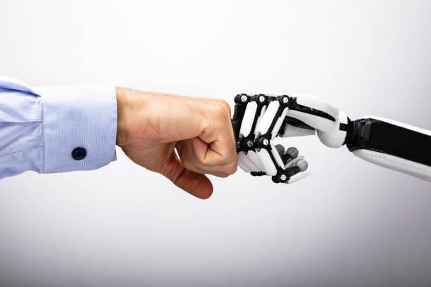 mano humana y robot haciendo fist bump - robot fotografías e imágenes de stock