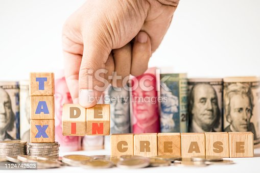 1024130248 istock photo Human hand array wooden cubes of Tax decrease and increase keyword on coins stacking with variety of banknote such as US dollar.Tax is cost of each business and every have to pay.Business concept. 1124742523