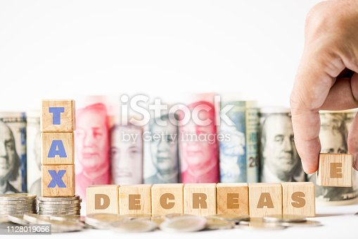 1024130248 istock photo Human hand array wooden cubes of Tax decrease keyword on coins stacking with variety of banknote such as yuan US dollar background. Tax is cost of each business and every have to pay.Business concept. 1128019056