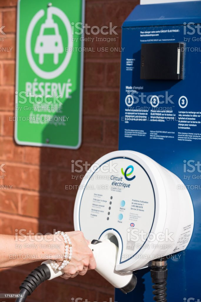 \'Laval, A!anada - September 3, 2012: Human hand Charging an electric...