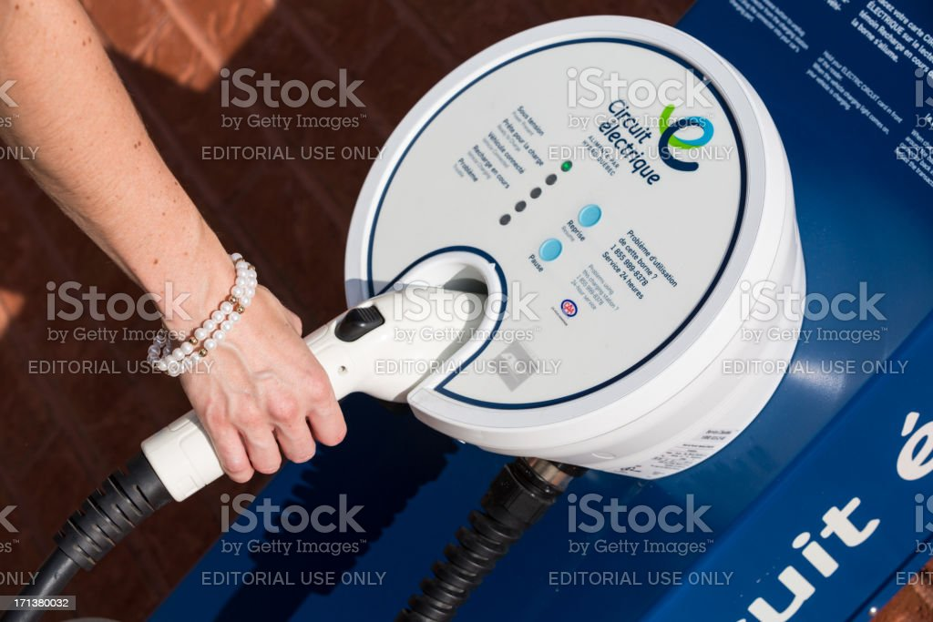 Human Hand Charging an Electric Vehicle at Charging Station royalty-free stock photo