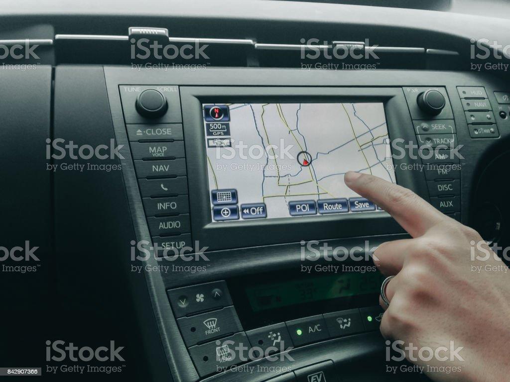 mänsklig handkontroll och peka på bil moniyor display med GPS navigator med inredning i lyxbil bildbanksfoto