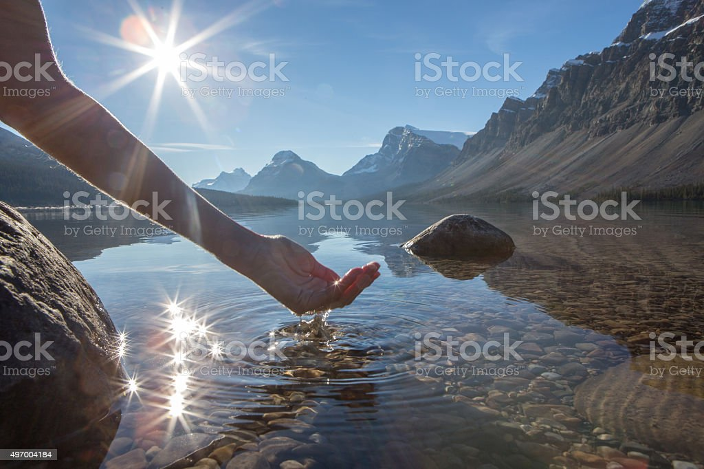 Human hand cupped to catch fresh water from mountain lake stock photo