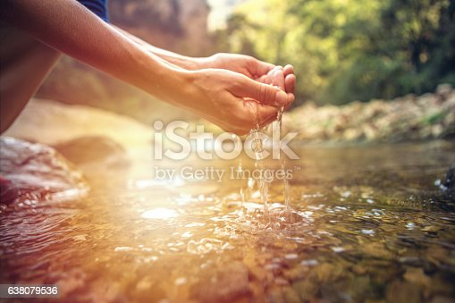 istock Human hand cupped to catch fresh water from river 638079536