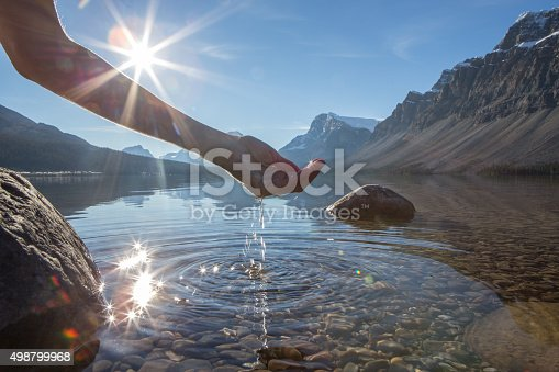 Human hand cupped to catch the fresh water from the lake, sunlight from sunset passing through the transparence of the water.