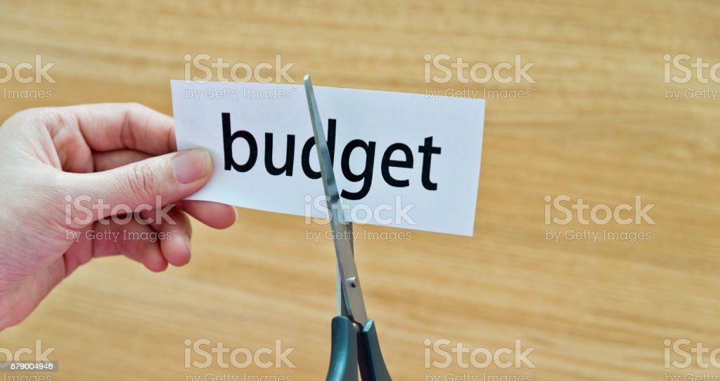 Human hand cutting the budget word stock photo