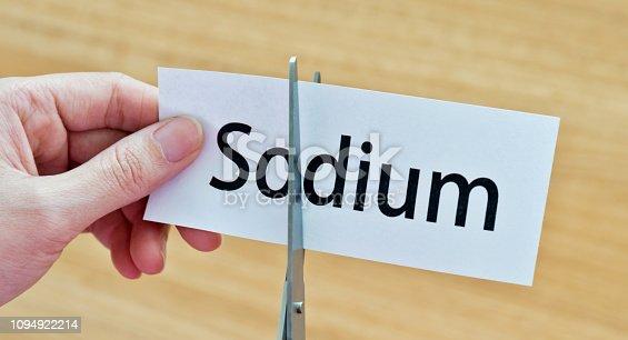 Human hand cutting the sodium word.