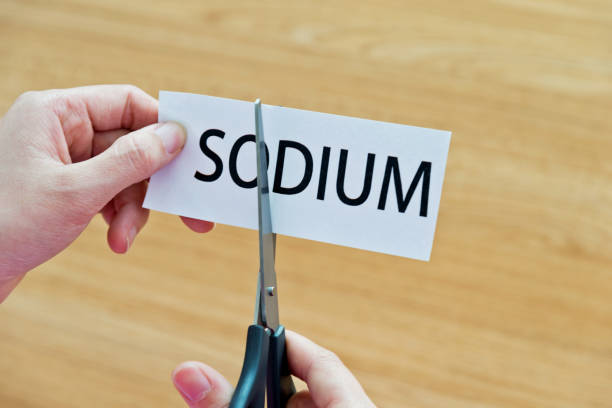 human hand cutting the sodium word - sodium stock pictures, royalty-free photos & images