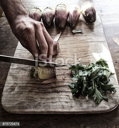 Hand of young adult man cutting vegetables on wooden cutting board