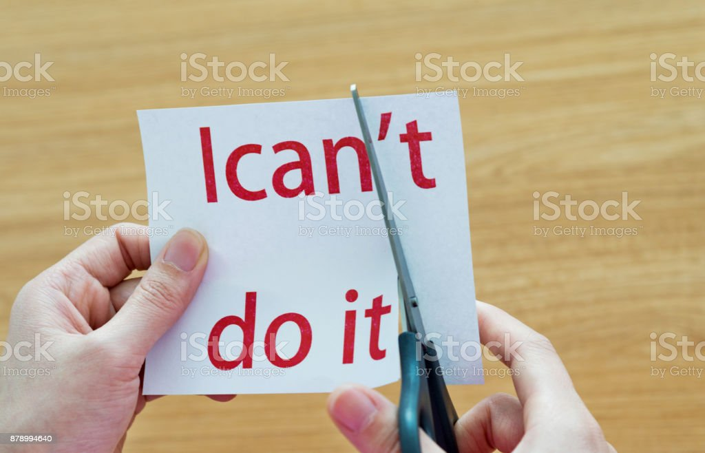 Human hand cutting word on paper can't become i can stock photo