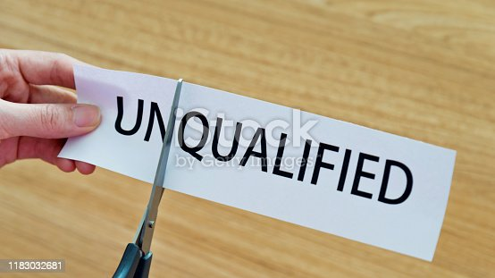 Human hand cutting word on paper unqualified become qualified.