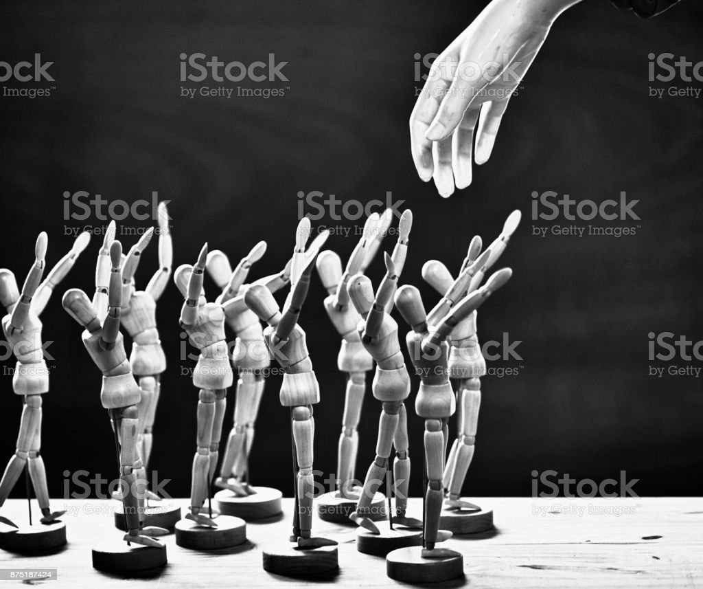 Human hand descends on group of awestruck wooden puppets stock photo