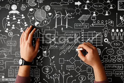 istock Human hand drawing business strategy on black desk 518675254