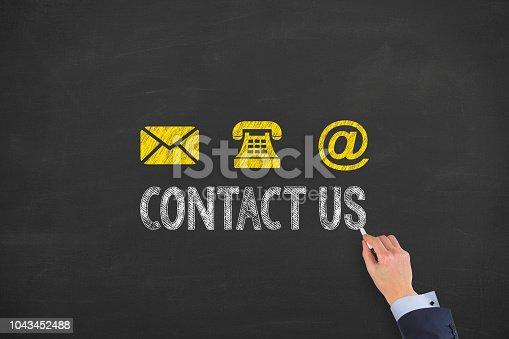 istock Human Hand Drawing Contact Us on Blackboard 1043452488