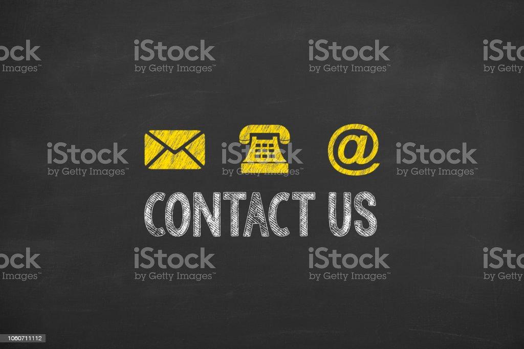 Human Hand Drawing Contact Us on Blackboard stock photo