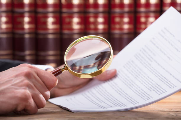Human Hand Examining Document Human Hand Examining Document Through Magnifying Glass legislation stock pictures, royalty-free photos & images