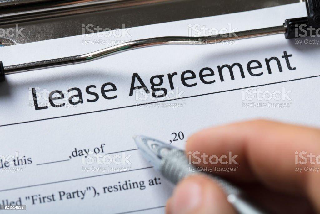 Menschliche Hand Lease Agreement Formular ausfüllen – Foto