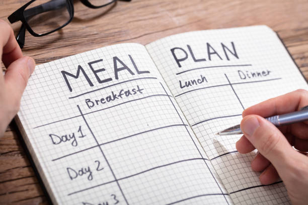 human hand filling meal plan in notebook - refeições imagens e fotografias de stock