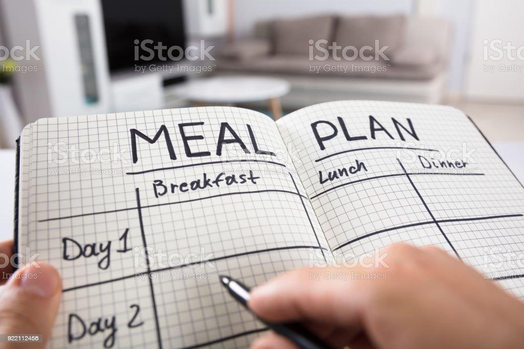 Mano humana Plan de comidas en el cuaderno de relleno foto de stock libre de derechos