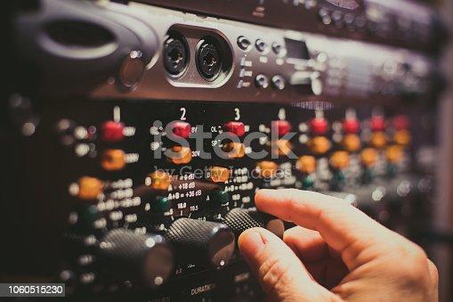 istock Human hand fine tuning levels on professional audio equipment 1060515230
