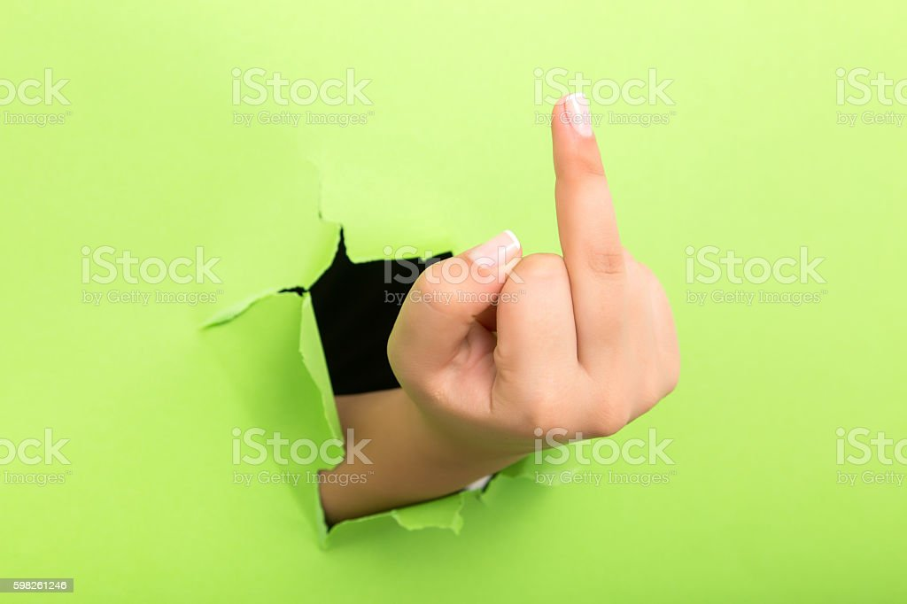 Human hand gesturing with middle finger through the paper hole...